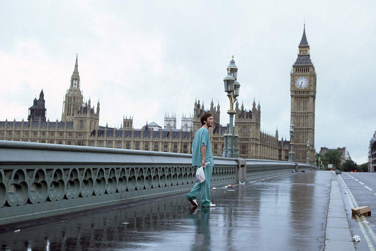 Jim (Cillian Murphy) marche dans une rue déserte de Londres avec des gommages