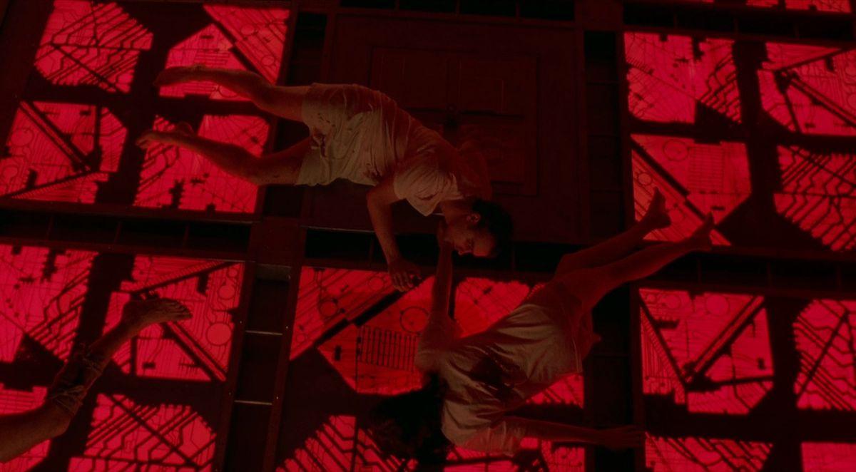 Deux personnages de Cube se tendent la main en position couchée sur un sol rouge rétroéclairé
