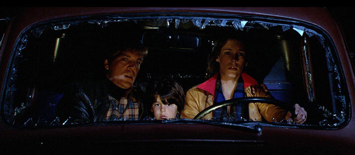 Elizabeth (Jamie Lee Curtis), Nick (Tom Atkins) et Andy (Ty Mitchell) regardent à travers un pare-brise éclaté dans une image de The Fog