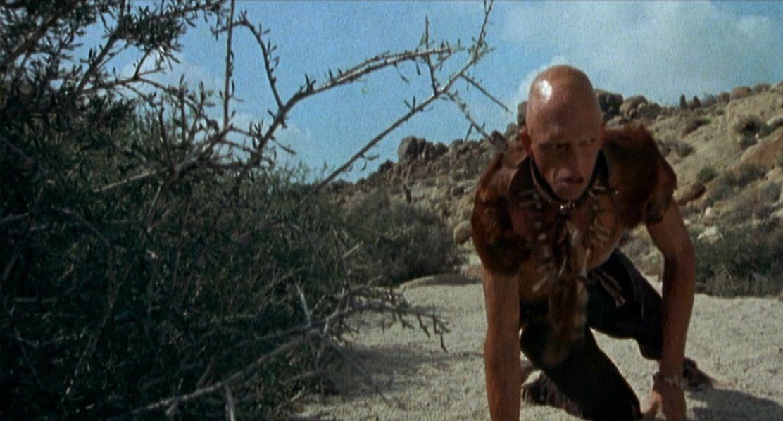 Pluton (Michael Berryman) s'accroupit derrière un buisson dans une image de The Hills Have Eyes