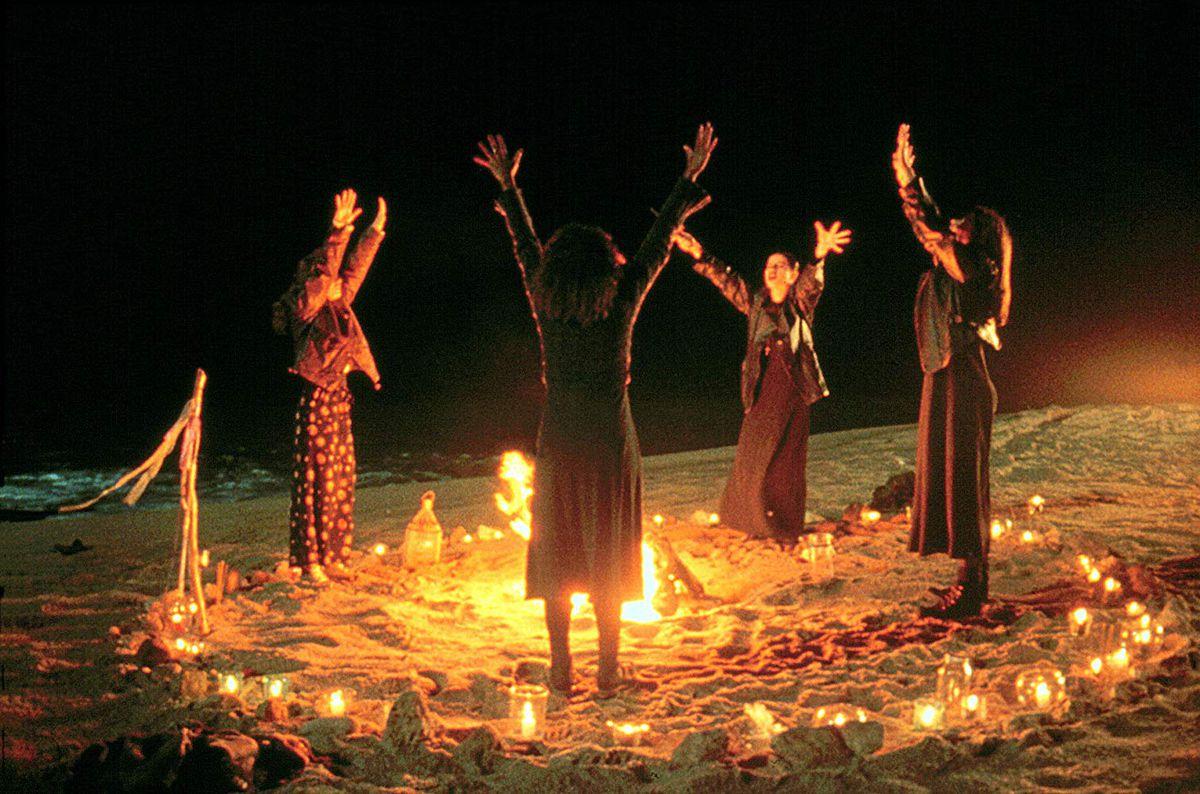 Les adolescentes sorcières de The Craft lèvent les bras autour d'un feu de joie