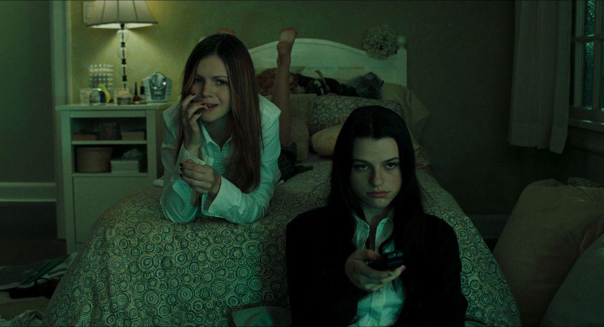Les adolescentes Katie (Amber Tamblyn) et Becca (Rachael Bella) regardent la télévision sur le lit de Katie sur une capture d'écran de The Ring